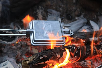 Cooking a pudgy pie over open fire